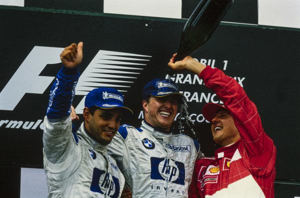 Ralf Schumacher, 1st position, celebrates on the podium with Juan Pablo Montoya, 2nd position, and Michael Schumacher, 3rd position.
