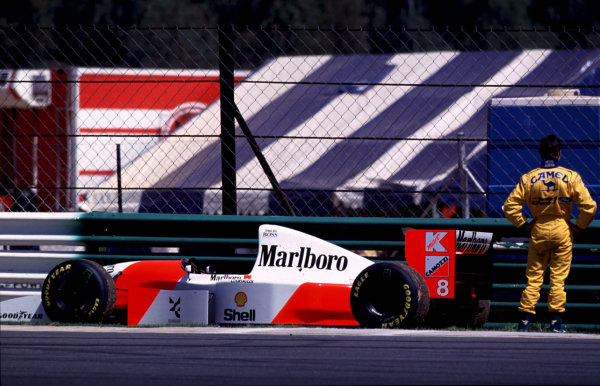 1993 South African Grand Prix Kyalami, South Africa 12-14 March 1993 Michael Schumacher (Benetton Ford), retired, studies the car of Ayrton Senna (McLaren MP4/8 Ford), 2nd position at the end of the race World Copyright - LAT Photographic