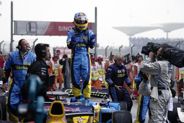 Fernando Alonso celebrates claiming pole position in parc fermé.