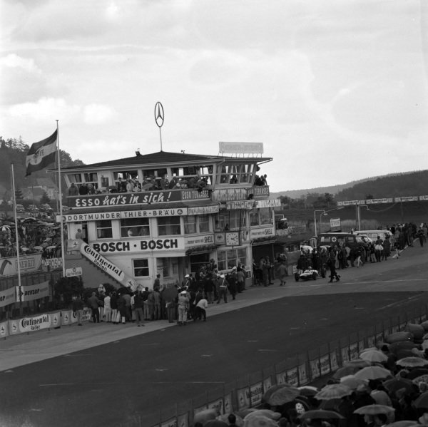 The main pit building, with John Surtees, Ferrari 156/63, parking up after taking the chequered flag.