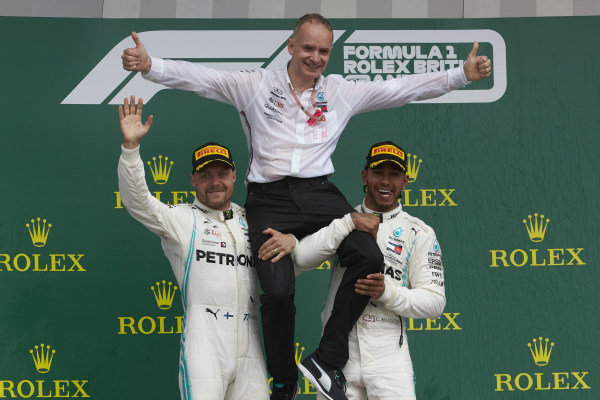 Valtteri Bottas, Mercedes AMG F1, 2nd position, and Lewis Hamilton, Mercedes AMG F1, 1st position, lift their team mate onto their shoulders on the podium