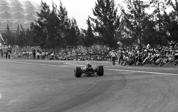 Graham Hill(GBR) Lotus 49B, on his way to victory with the crowd sat at the edge of the track  Mexican GP, Mexico City, 3 November 1968