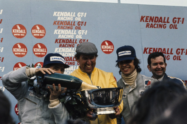 Winner Jackie Stewart fills his trophy with champagne with team boss Ken Tyrrell and teammate François Cevert, 2nd position.