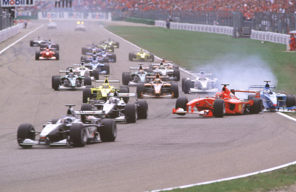 2000 German Grand Prix. Hockenheim, Germany. 28-30 July 2000. Mika Hakkinen leads David Coulthard (both McLaren MP4/15 Mercedes) as Michael Schumacher (Ferrari F1-2000) pulls across into Giancarlo Fisichella (Benetton B200 Playlife) on the approach to the Nordkurve at the start, resulting in a crash. World Copyright - Coates/LAT Photographic crash sequence 05. ref: 35mm A05