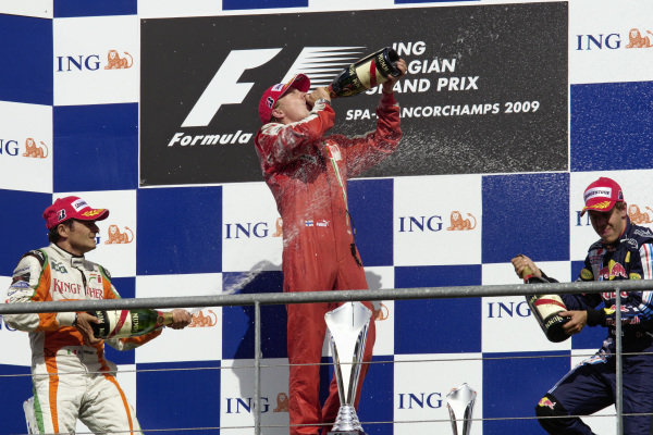Winner Kimi Räikkönen chooses to drink his champagne while Giancarlo Fisichella, 2nd position, and Sebastian Vettel, 3rd position, spray it in celebration.