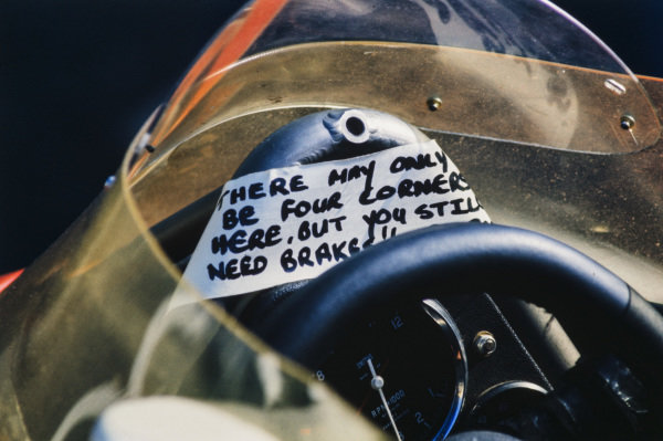 "An amusing message is left above the steering wheel of a McLaren M23: ""There may only be four corners here, but you still need brakes!!"""