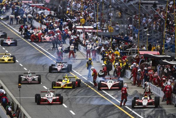 Cars leave the pit lane. Al Unser Jr, Kelley Racing, Dallara IR-03 Toyota, leads Scott Sharp, Kelley Racing, Dallara IR-03 Toyota, Toranosuke Takagi, Mo Nunn Racing, G-Force GF05 Toyota, and Kenny Bräck, Team Rahal, Dallara IR-03 Honda. Dan Wheldon, Andretti Green Racing, Dallara IR-03 Honda, and Tomas Scheckter, Ganassi Racing, G-Force GF05 Toyota, complete their pitstops.
