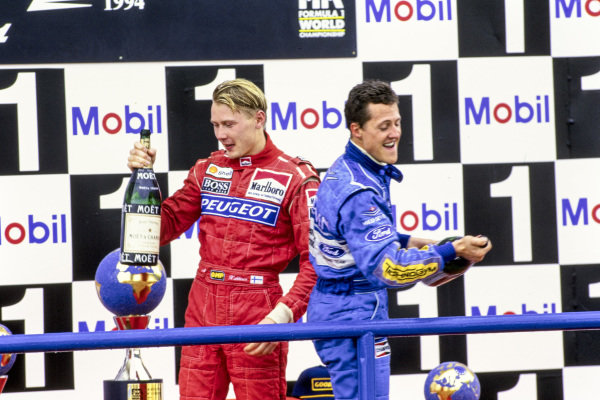 Mika Häkkinen, 3rd position, and Michael Schumacher, 1st position, celebrate with champagne on the podium.