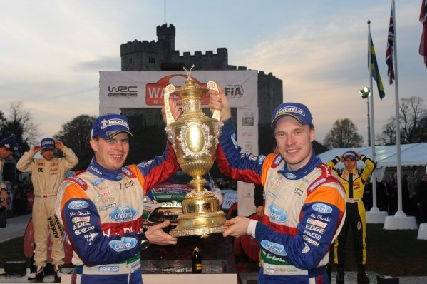 Jari-Matti Latvala (FIN) and Miikka Anttila (FIN) with the winners' trophy on the podium in Cardiff Castle.