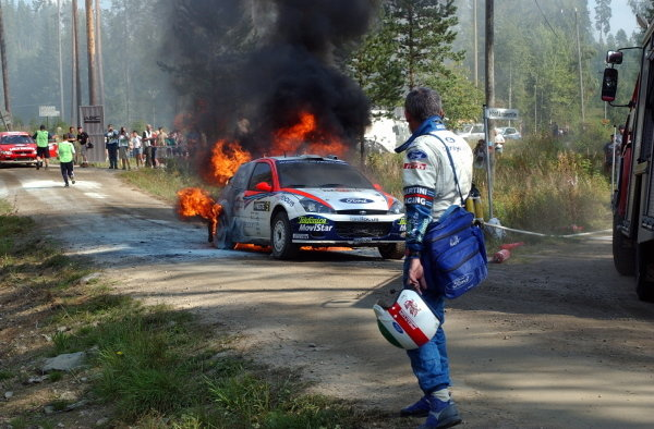 Co-driver Nicky Grist (GBR) watches the Ford Focus RS WRC burn after a loose hyrdaulic cable caught fire.FIA World Rally Championship, Rd9, Neste Rally Finland, Day Three, Finland. 11 August 2002.DIGITAL IMAGE