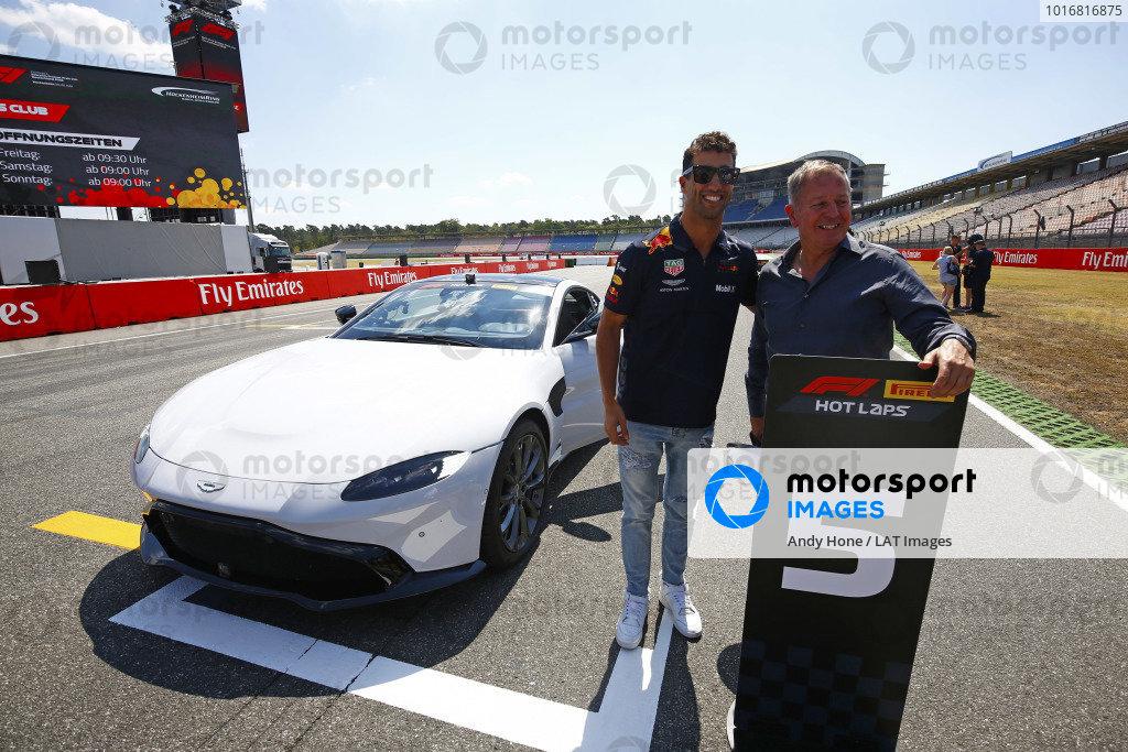 Daniel Ricciardo, Red Bull Racing, and Martin Brundle pose with a Pirelli Hot laps Aston Martin.