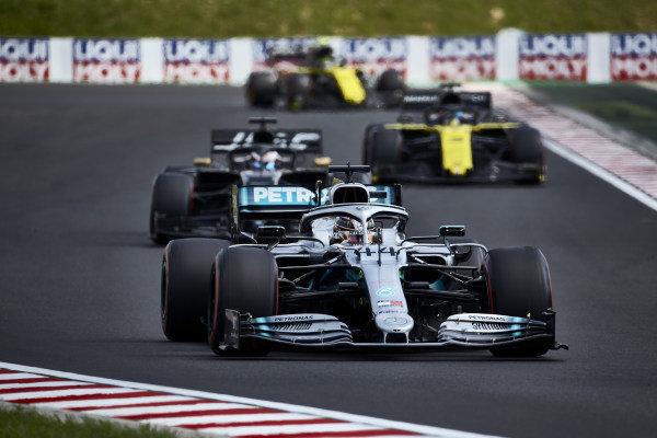 Lewis Hamilton, Mercedes AMG F1 W10, leads Romain Grosjean, Haas VF-19, and Daniel Ricciardo, Renault R.S.19