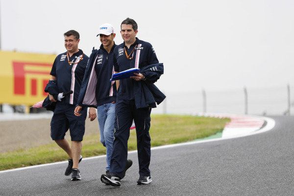 Esteban Ocon, Racing Point Force India, walks the track with members of his team.
