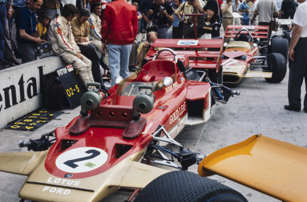 Jochen Rindt and Emerson Fittipaldi sit on the pitwall in front of their Lotus 72C Ford and Lotus 49C Ford respectively.