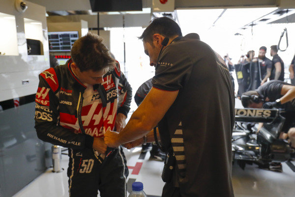 Louis Deletraz, Haas test and development driver, adjusts his overalls in the team's garage.