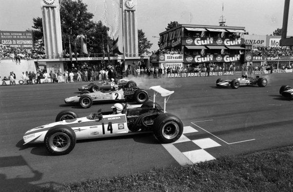 John Surtees, Honda RA301, leads Bruce McLaren, McLaren M7A Ford, and Chris Amon, Ferrari 312, at the start.