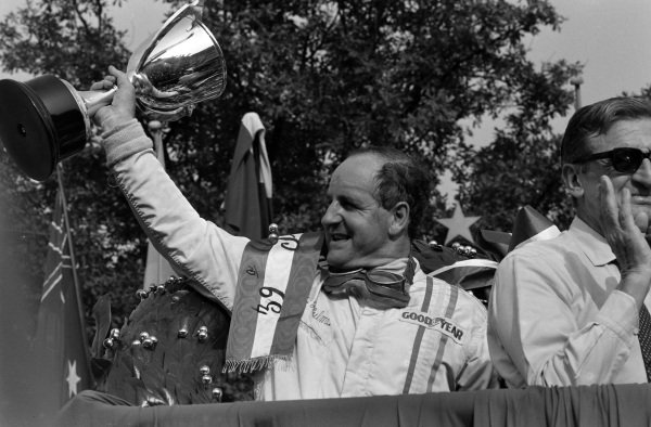 Denny Hulme, 1st position, celebrates on the podium.