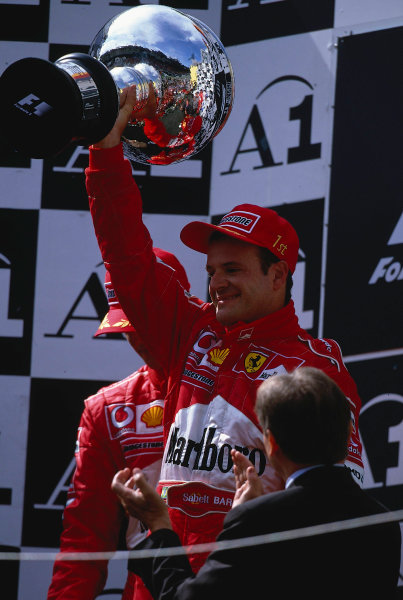 2002 Austrian Grand Prix.A1-Ring, Zeltweg, Austria.10-12 May 2002.Rubens Barrichello (Ferrari) celebrates his 2nd position on the podium, even though he is holding the winners trophy aloft after being handed it by Michael Schumacher, who was unhappy about the team orders which had ensued in the race.Ref-02 AUT 33.World Copyright - LAT Photographic