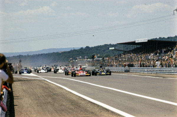 Pole sitter Niki Lauda, Ferrari 312B3, leads Ronnie Peterson, Lotus 72E Ford, and the rest of the field at the start.