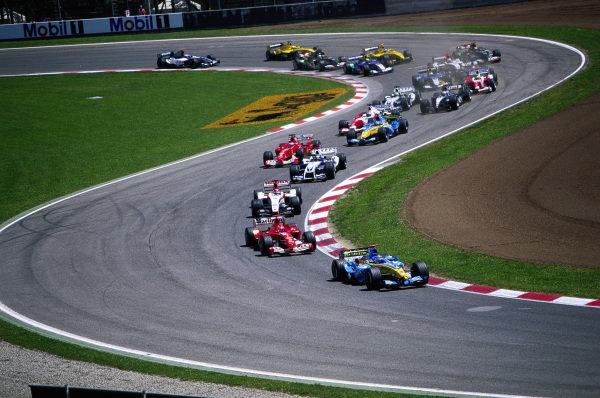 Jarno Trulli, Renault R24, leads Michael Schumacher, Ferrari F2004, Takuma Sato, BAR 006 Honda. Juan Pablo Montoya, Williams FW26 BMW, Rubens Barrichello, Ferrari F2004, Fernando Alonso, Renault R24, and Olivier Panis, Toyota TF104, at the start.