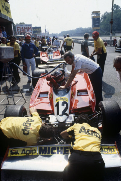 Gilles Villeneuve, Ferrari 312T3 sits in the pits as mechanics work on the front wing. Team mate Carlos Reutemann waits behind him.