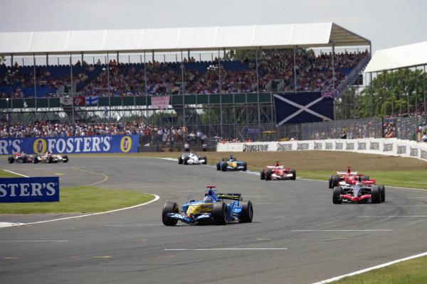 Fernando Alonso, Renault R26 leads Kimi Räikkönen, McLaren MP4-21 Mercedes and Michael Schumacher, Ferrari 248 F1 after the safety car restart.