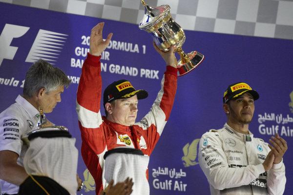 Kimi Räikkönen, 2nd position celebrates with the trophy, Lewis Hamilton, 1st position.