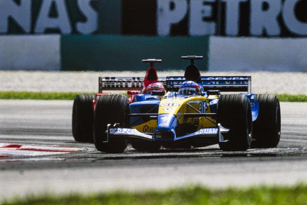 Fernando Alonso, Renault R23, leads Rubens Barrichello, Ferrari F2002.