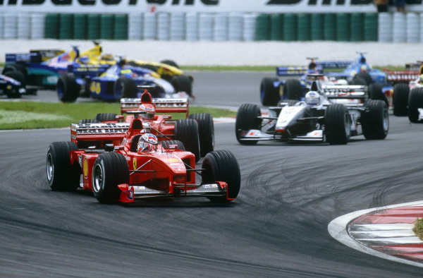 Sepang, Kuala Lumpur, Malaysia. 15-17 October 1999. Michael Schumacher leads Eddie Irvine (both Ferrari F399) and David Coulthard (McLaren MP4/14 Mercedes) at the start of the race.  Ref: 99MAL14. World Copyright - LAT Photographic