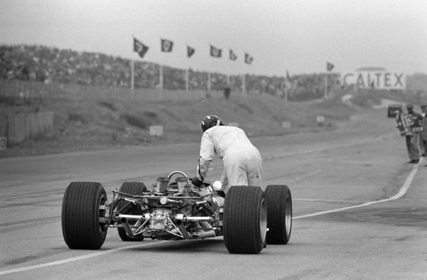 Graham Hill pushes his Lotus 49 Ford back to the pit lane.