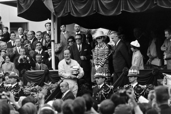 Denny Hulme, 1st position, on the podium with Prince Rainier, Grace Kelly, Princess Caroline and Louis Chiron.