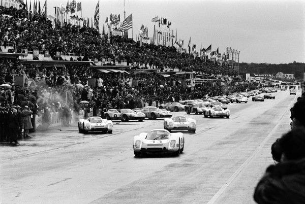 Rolf Stommelen / Jochen Neerpasch, Porsche System Engineering, Porsche 908 (car #33), leads the field away at the start.