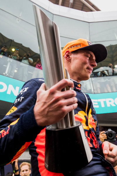 Sepang International Circuit, Sepang, Malaysia. Sunday 1 October 2017. Max Verstappen, Red Bull, 1st Position, celebrates with his team and his trophy. World Copyright: Zak Mauger/LAT Images  ref: Digital Image _56I3740