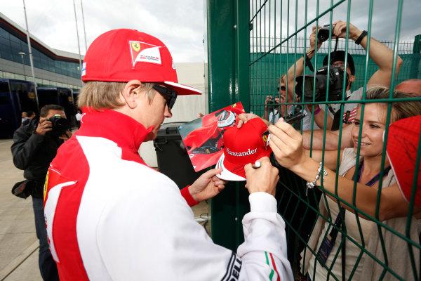 Silverstone, Northamptonshire, England. Saturday 5 July 2014. Kimi Raikkonen, Ferrari, signs autographs for fans. World Copyright: Andrew Ferraro/LAT Photographic. ref: Digital Image _FER0420