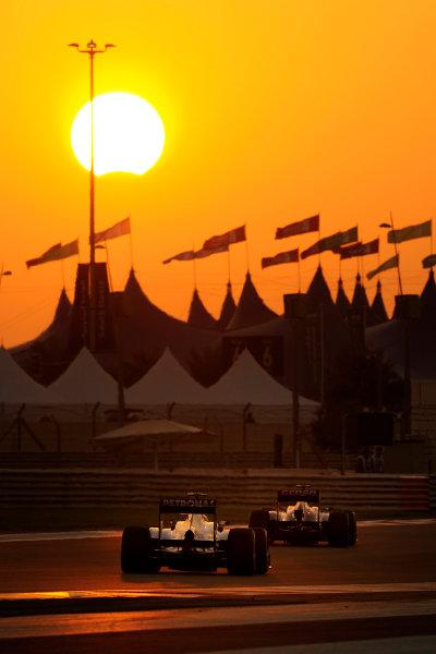 Yas Marina Circuit, Abu Dhabi, United Arab Emirates. Sunday 3rd November 2013.  Jean-Eric Vergne, Toro Rosso STR8 Ferrari, leads Lewis Hamilton, Mercedes W04, in front of a partial eclipse at sunset.  World Copyright: Steve Etherington/LAT Photographic. ref: Digital Image ABD-RACE-3074 copy
