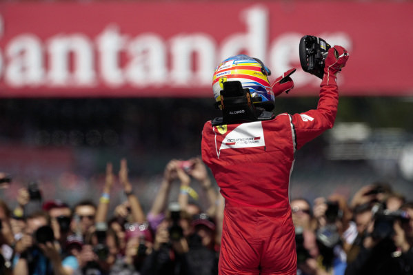 Fernando Alonso points at his steering wheel in Parc Ferme.