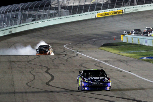 20-22 November, 2009, Miami Beach, Florida USA2009 NASCAR champion Jimmie Johnson drives down the front straight while Denny Hamlin celebrates winning the race with a burn out©2009 Lesley Ann Miller, USALAT Photographic