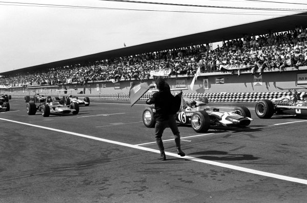 The flag man gets the race underway, led from pole position by Jo Siffert (SUI) Rob Walker Lotus 49B.  Mexican Grand Prix, Mexico City, 3 November 1968.