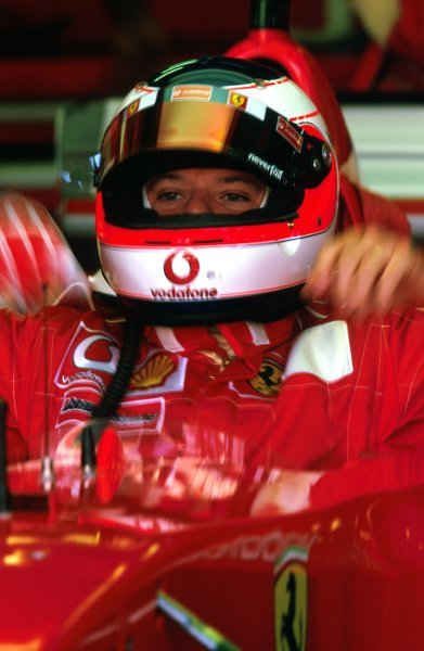 Rubens Barrichello (BRA) squeezes into the cockpit of his Ferrari F2002.