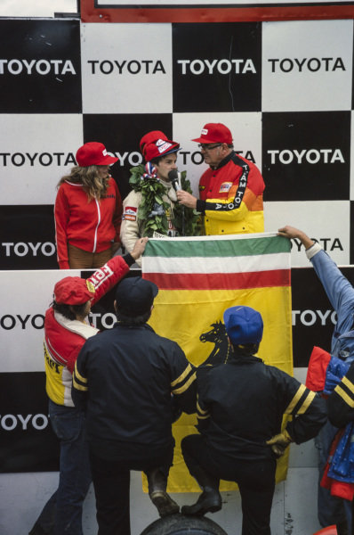 Gilles Villeneuve gets interviewed on the podium while team members proudly hold up a Ferrari flag.