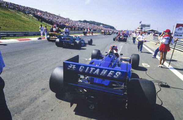 Piercarlo Ghinzani, Ligier JS29C Megatron, on the grid as Ivan Capelli, March 871 Ford, drives to his grid spot.