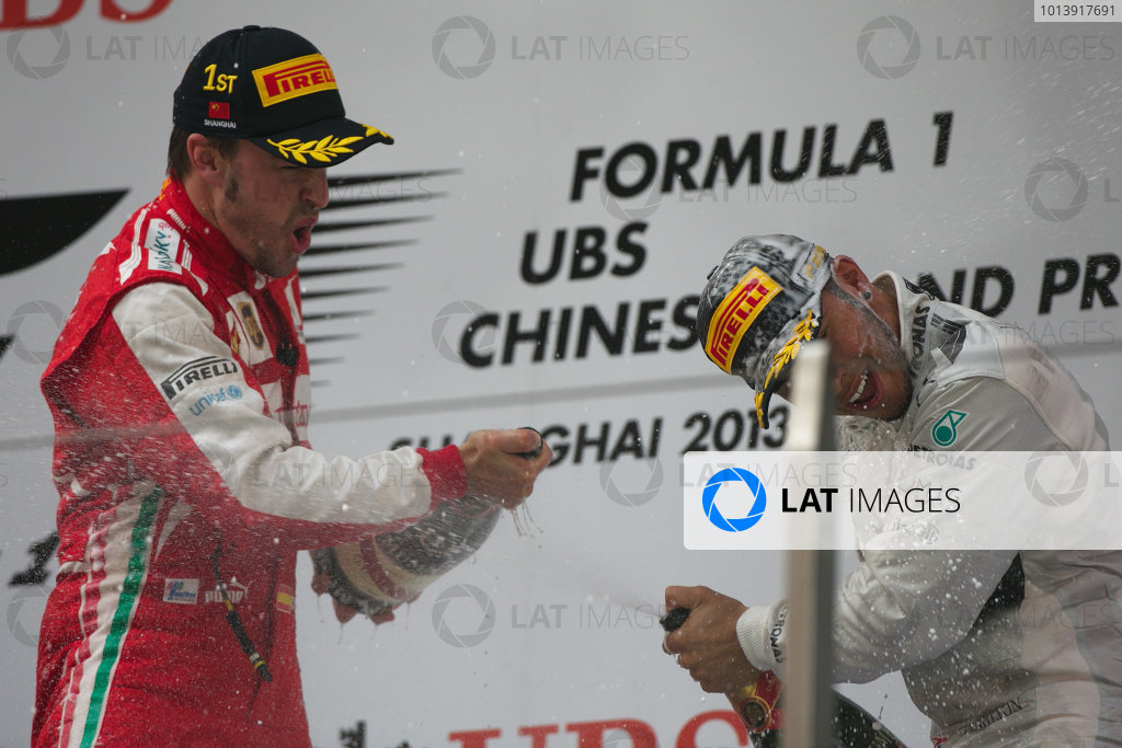 Shanghai International Circuit, Shanghai, China Sunday 14th April 2013 Fernando Alonso, Ferrari, 1st position, and Lewis Hamilton, Mercedes AMG, 3rd position, celebrate on the podium with Champagne. World Copyright: Andy Hone/LAT Photographic ref: Digital Image HONZ7923