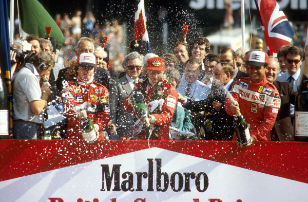 Brands Hatch, England.16-18 July 1982.Niki Lauda (McLaren Ford) 1st position, Didier Pironi (Ferrari) 2nd position and Patrick Tambay (Ferrari) 3rd position on the podium.Ref-82 GB 01.World Copyright - LAT Photographic