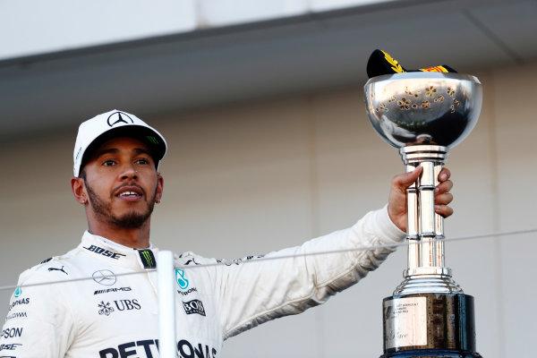 Suzuka Circuit, Japan. Sunday 08 October 2017. Lewis Hamilton, Mercedes AMG, celebrates with his winner's trophy on the podium. World Copyright: Glenn Dunbar/LAT Images  ref: Digital Image _X4I8975