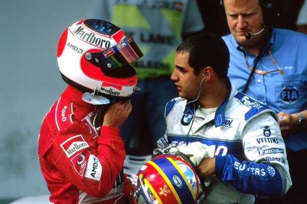 Second place driver Rubens Barrichello (BRA) Ferrari, left, chats with Juan Pablo Montoya (COL) Williams, right, in parc ferme after the race. Austrian Grand Prix, Rd6, A1-Ring, Austria. 13 May 2002. BEST IMAGE
