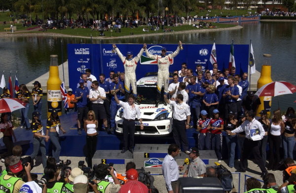 The rally winning crew of Michael Park (GBR) and Markko Martin (EST) Ford Focus RS WRC 03 celebrate victory on the podium with Malcolm Wilson (GBR) Ford Team Boss.