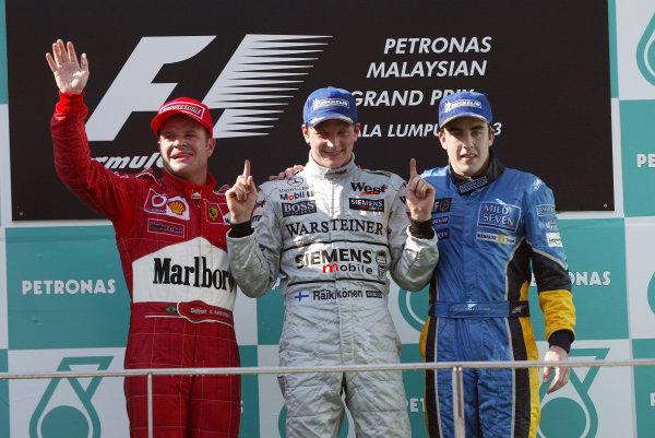 2003 Malaysian Grand Prix. Sepang, Kuala Lumpur, Malaysia.21-23 March 2003.Rubens Barrichello (Ferrari) 2nd position, Kimi Raikkonen (McLaren Mercedes) 1st position and Fernando Alonso (Renault) 3rd position, celebrate on the podium.World Copyright - Steve Etherington/LAT Photographic ref: Digital Image Only