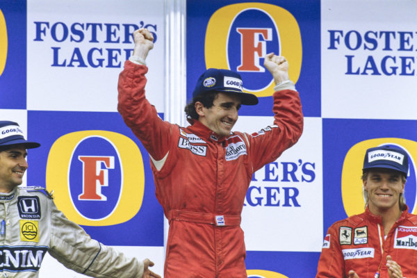 Alain Prost, 1st position, celebrates an unlikely second world championship alongside Nelson Piquet, 2nd position, and Stefan Johansson, 3rd position, on the podium.