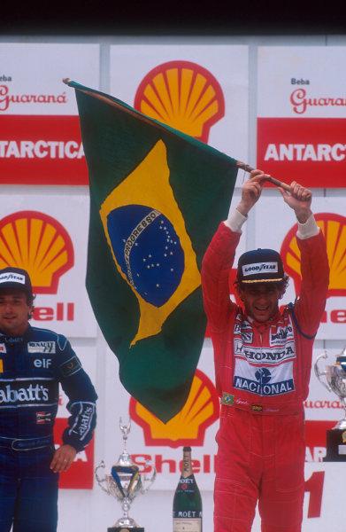 1991 Brazilian Grand Prix.Interlagos, Sao Paulo, Brazil.22-24 March 1991.Ayrton Senna (McLaren Honda) celebrates 1st position on the podium with Riccardo Patrese (Williams Renault) 2nd position behind.Ref-91 BRA 10.World Copyright - LAT Photographic