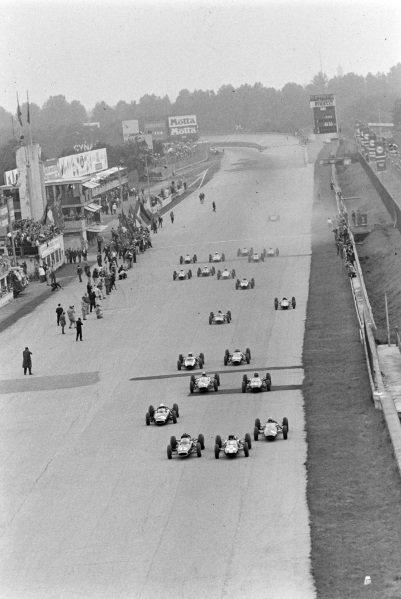 Jim Clark, Lotus 25 Climax, battles with Graham Hill, BRM P61, down the Rettifilo Tribune at the start. They lead John Surtees, Ferrari 156 Aero, Richie Ginther, BRM P57, Dan Gurney, Brabham BT7 Climax, Lorenzo Bandini, Ferrari 156/63, Bruce McLaren, Cooper T66 Climax, and Jack Brabham, Brabham BT3 Climax.